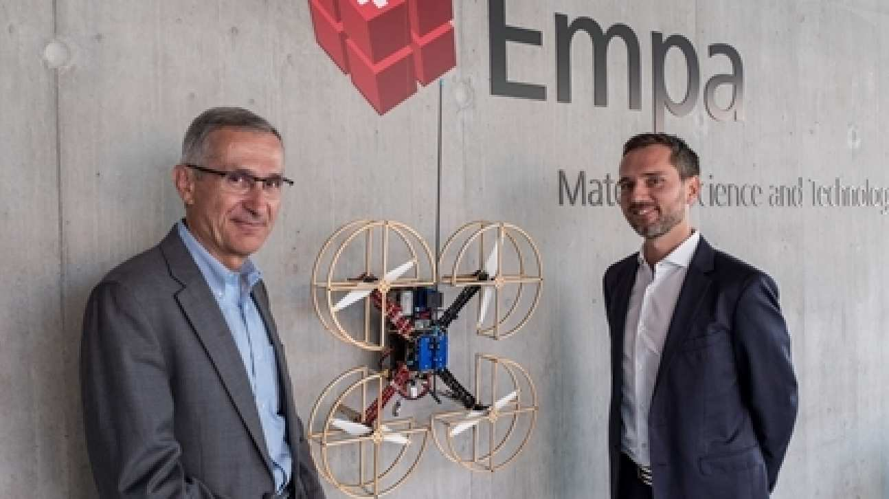 Two men with a drone attached to the wall between them