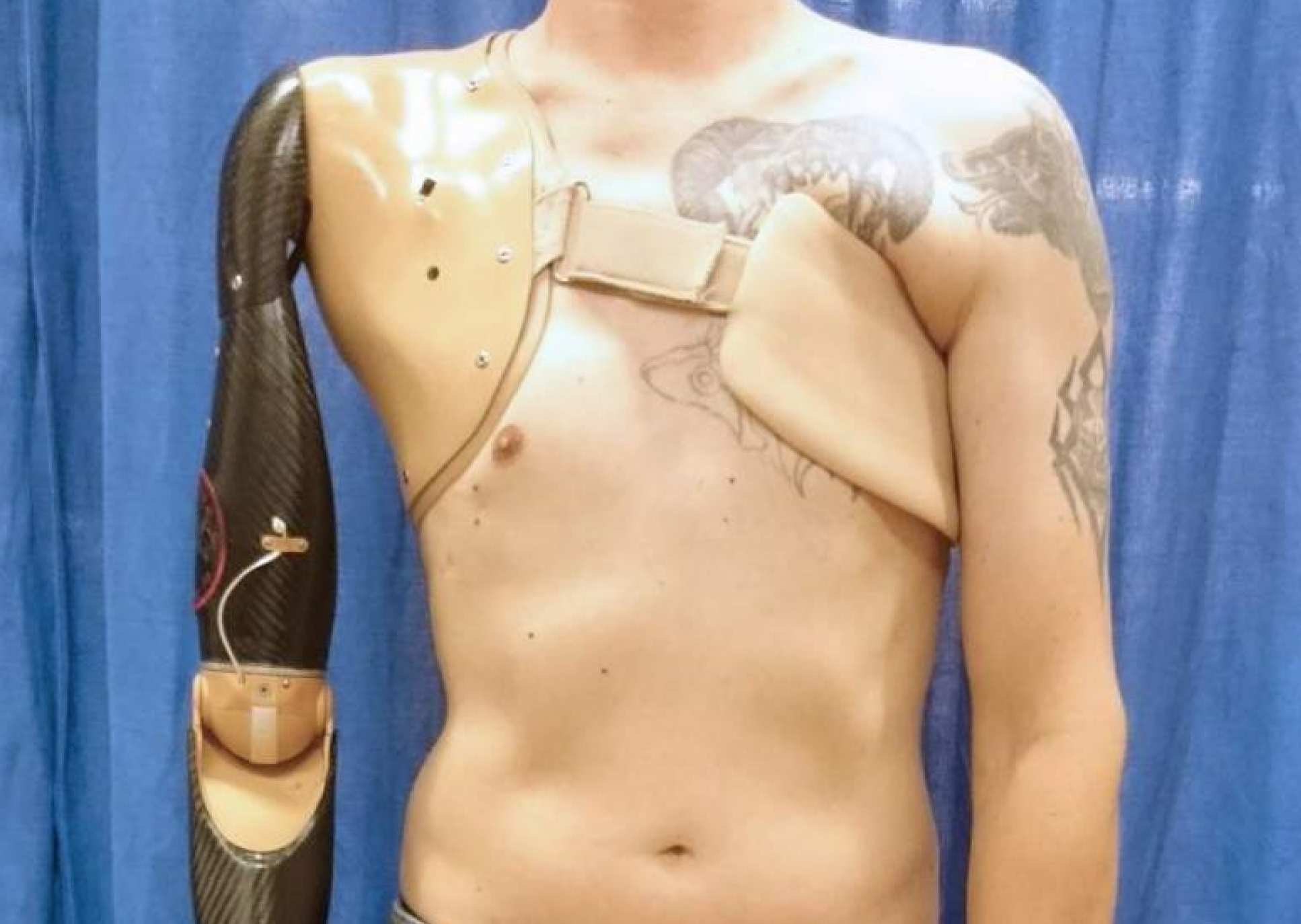 Torso of a man with a robotic arm strapped to his chest