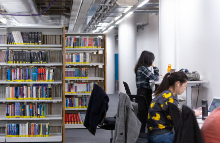 Students studying in the central library with book cases in the background