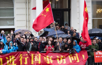 A crowd of Chinese people with flags stand on Exhibition Road