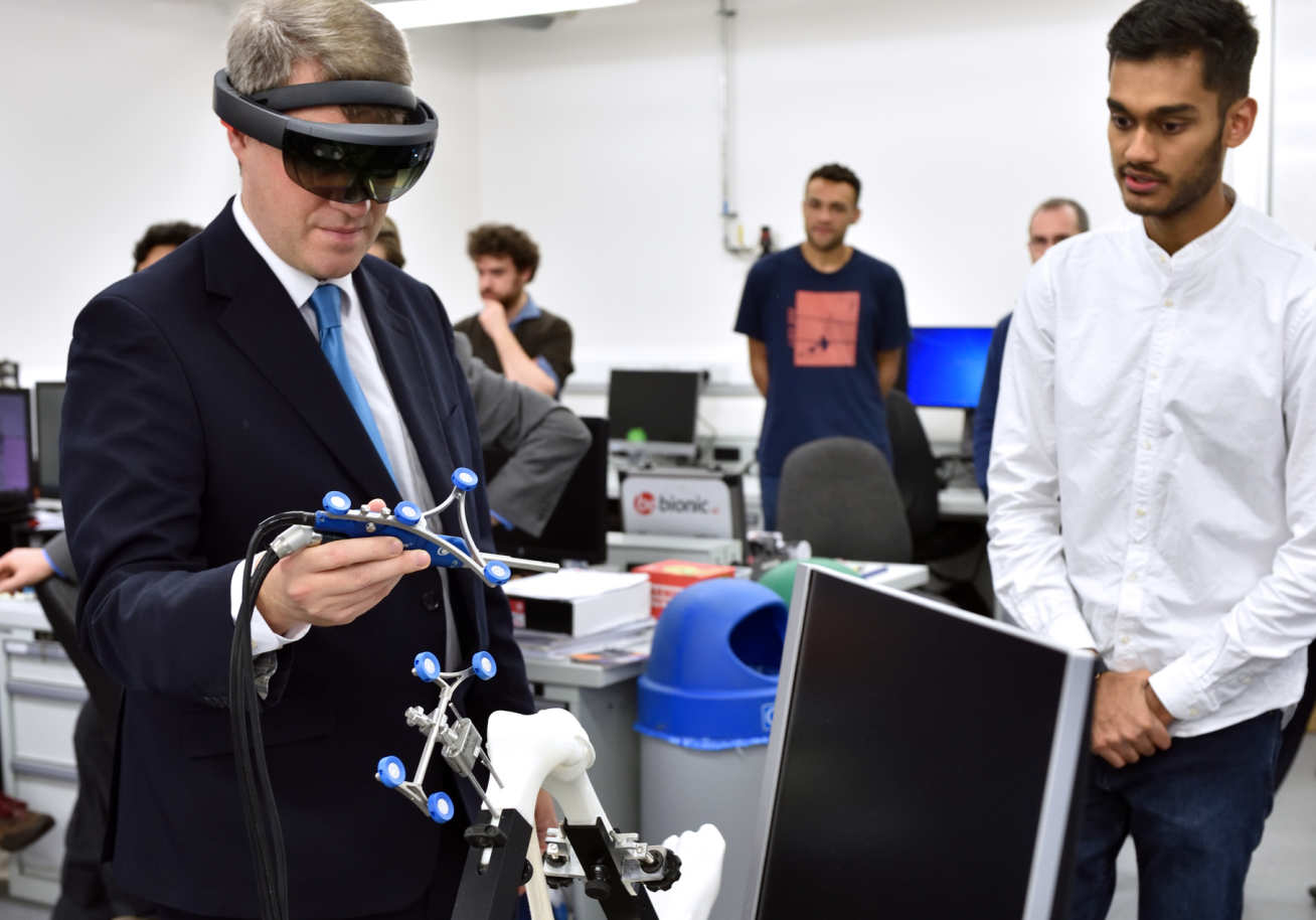 The minister trying out a virtual reality headset with a student