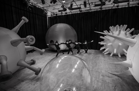 Performers dancing and surrounded by large inflatable cells