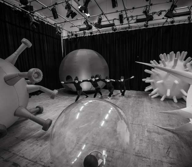 Dancers interlinked among the inflatable cell set