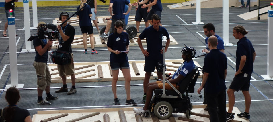 Team Imperial pilot Sivashankar Sivakanthan steering an eye-controlled wheelchair over an uneven surface at the Cybathlon Rehearsal 2015 event in Zurich.