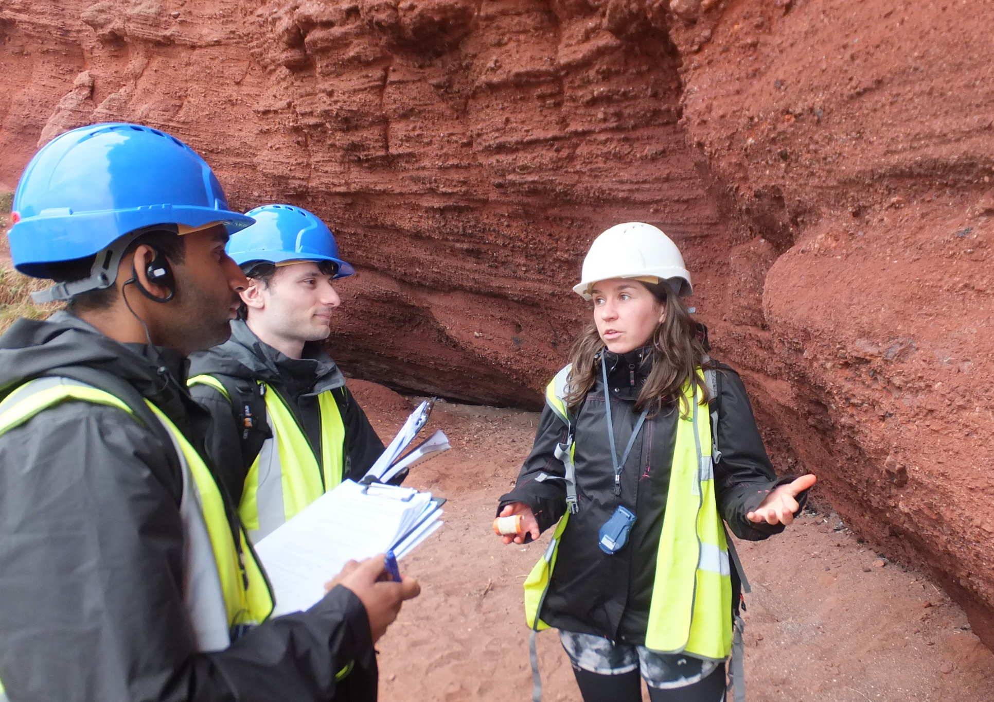 MSc Petroleum Engineering students stand on the beach by a red cliff and discuss its geological features