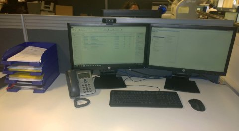 Clean desk with monitors, keyboard, mouse, telephone and intrays