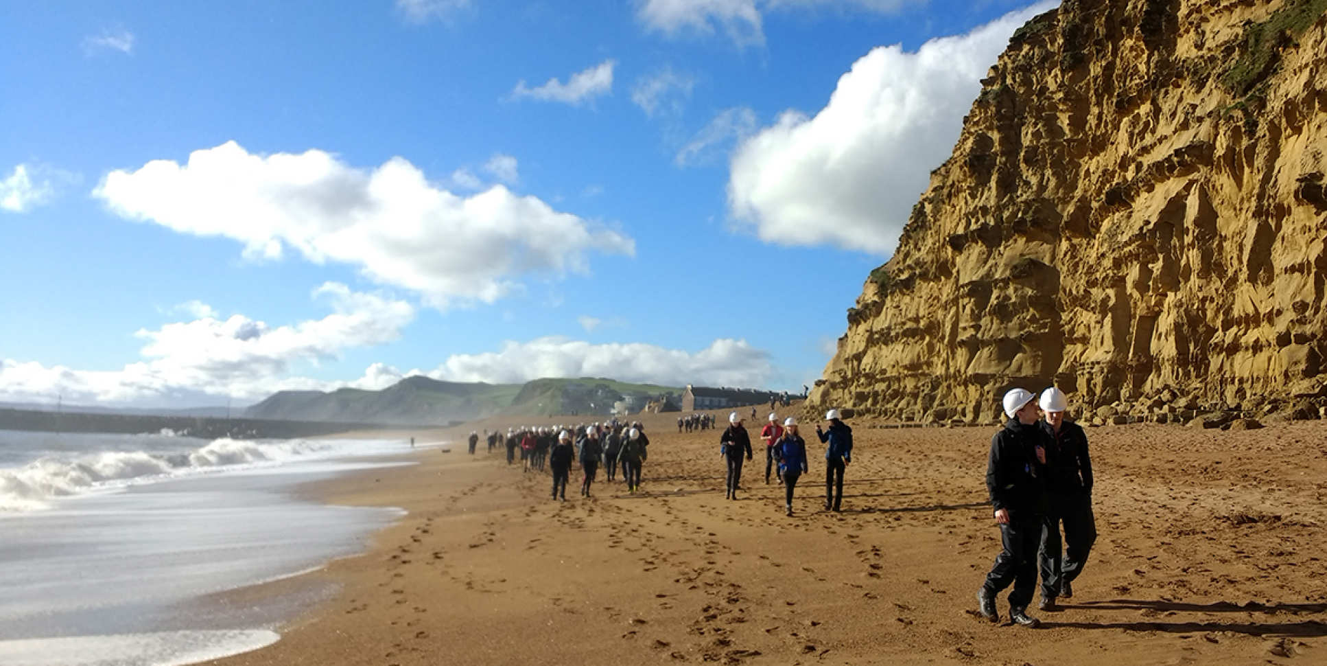 Students walk on the beach next to cliffs during Dorset 2017 undergraduate field trip