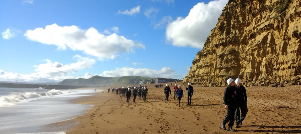 Students walk on the beach by a cliff in the sunshine on a Dorset field trip