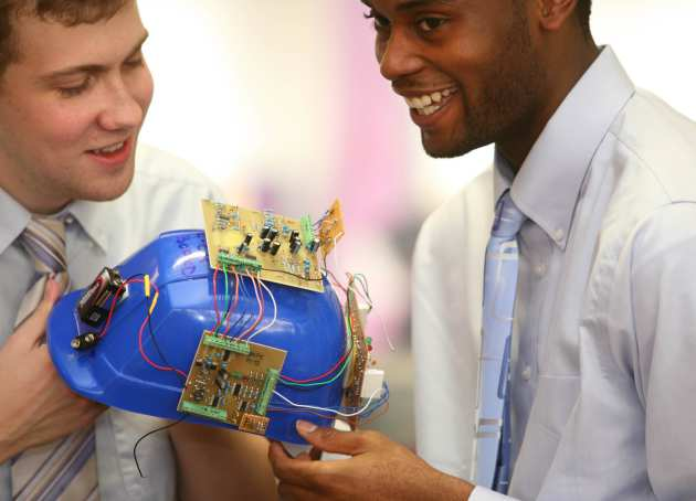two students looking at their group project hardware