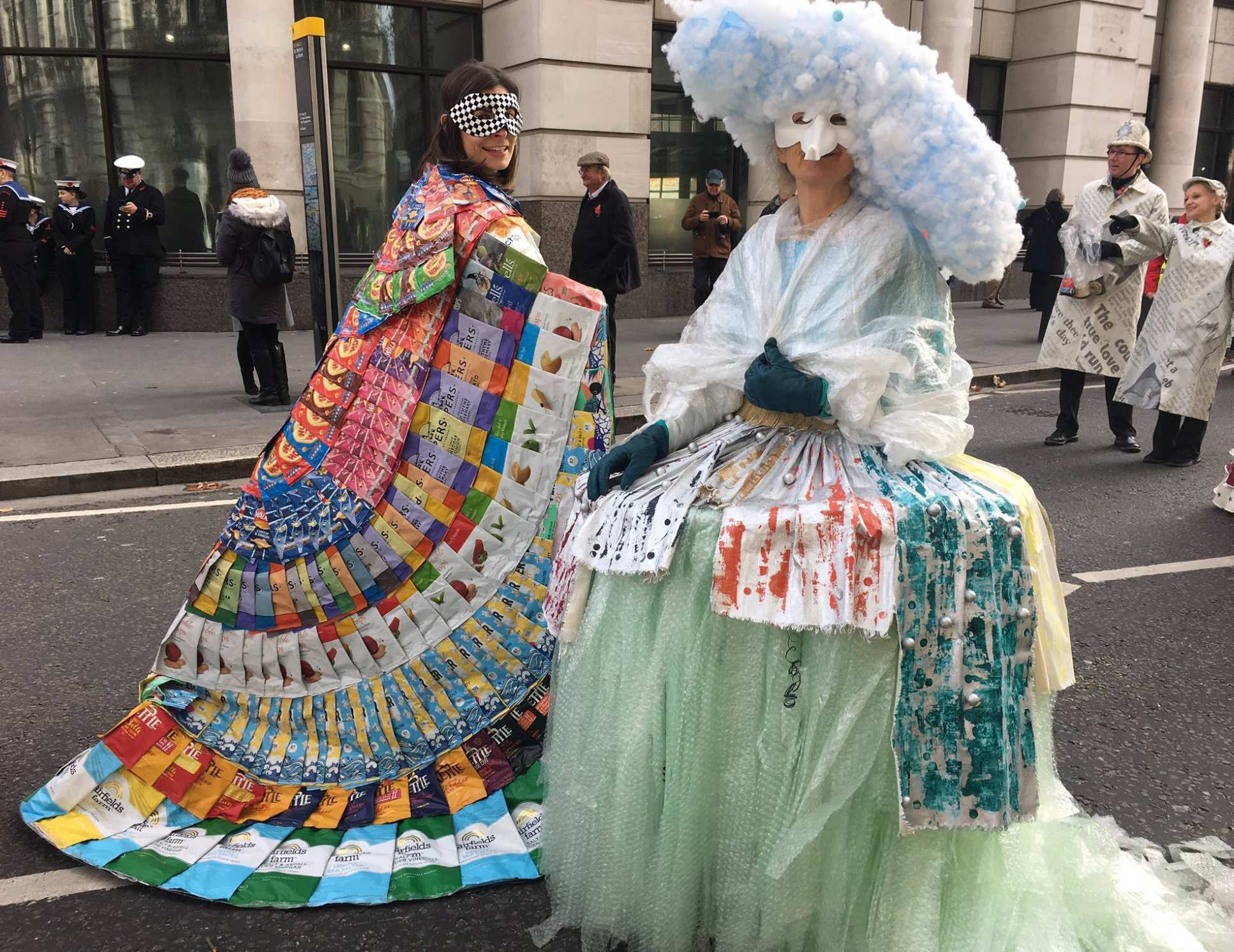 Two people wear cloaks made of trash. Left: crisp packets. Right: discarded plastics including bubble wrap and polystyrene
