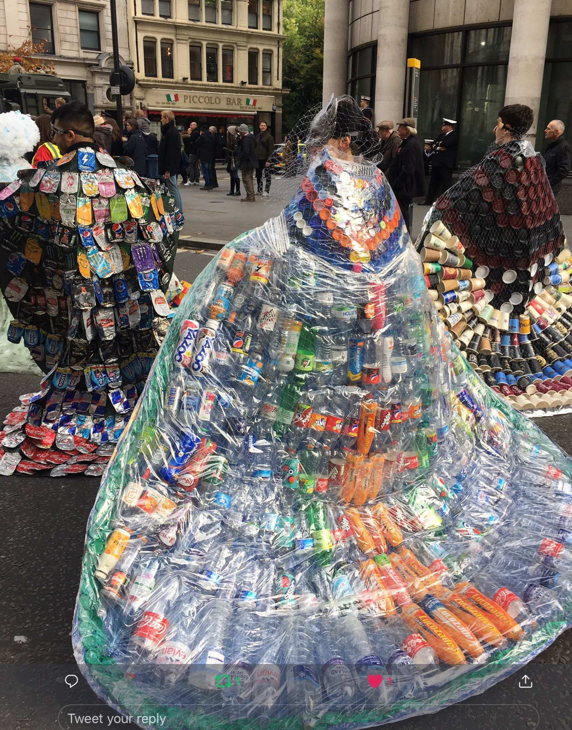 Three people wear cloaks made of trash. Left: crushed drinks cans. Centre: Plastic bottles. Right: disposable cups