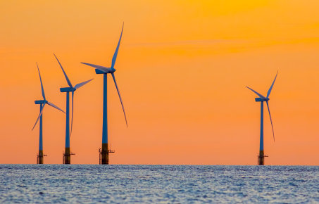 offshore wind turbines against an orange sky