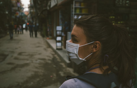 woman wearing a air filter mask in a city street