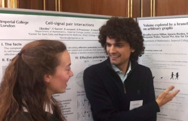 People talking at a workshop in front of posters of their research.