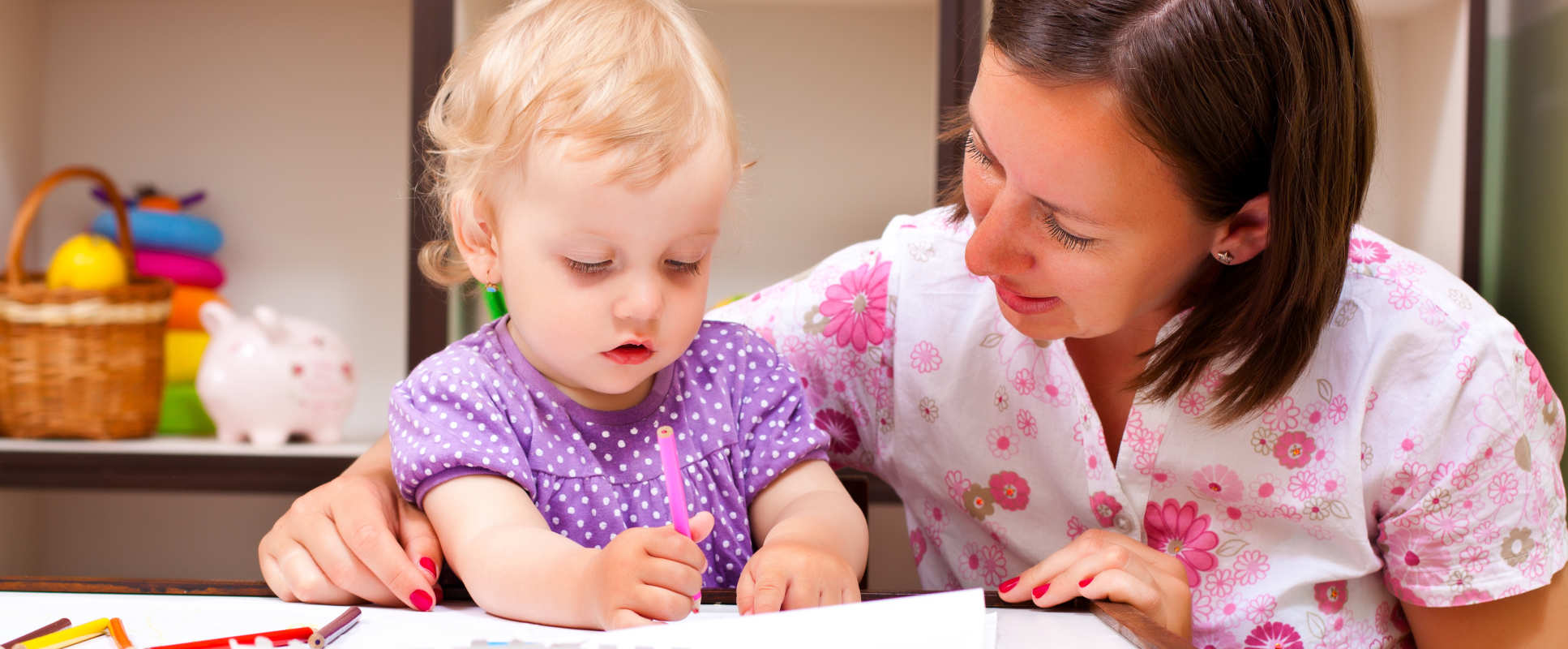 Mother looking at book with young child of two years