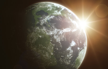 Earth from space, with sun showing behind