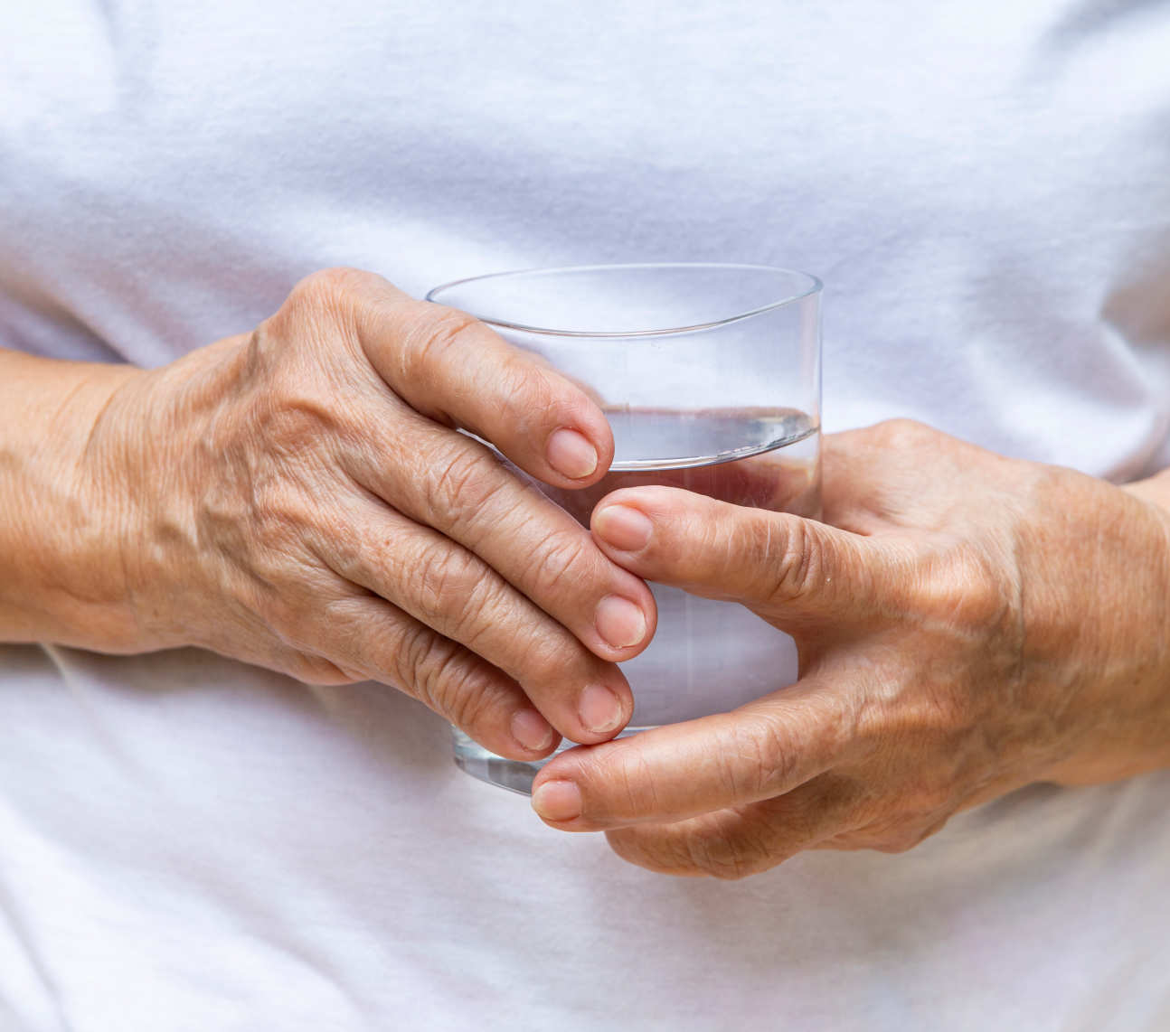 Elderly person's hand holding a glass