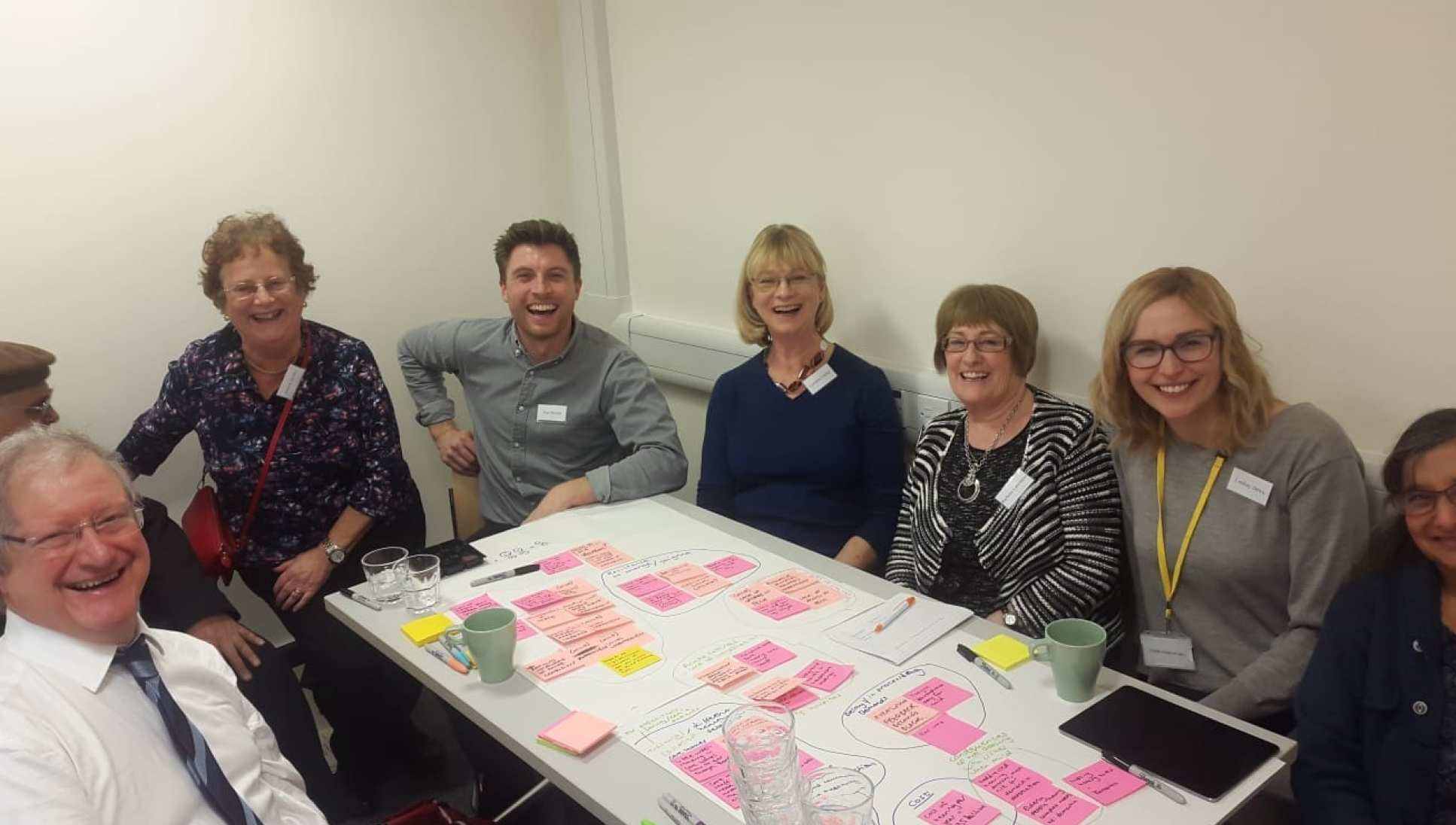 A photograph of members of the workshop sitting around a table with post it notes