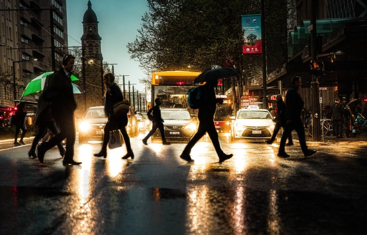People crossing a busy road in the rain at dusk