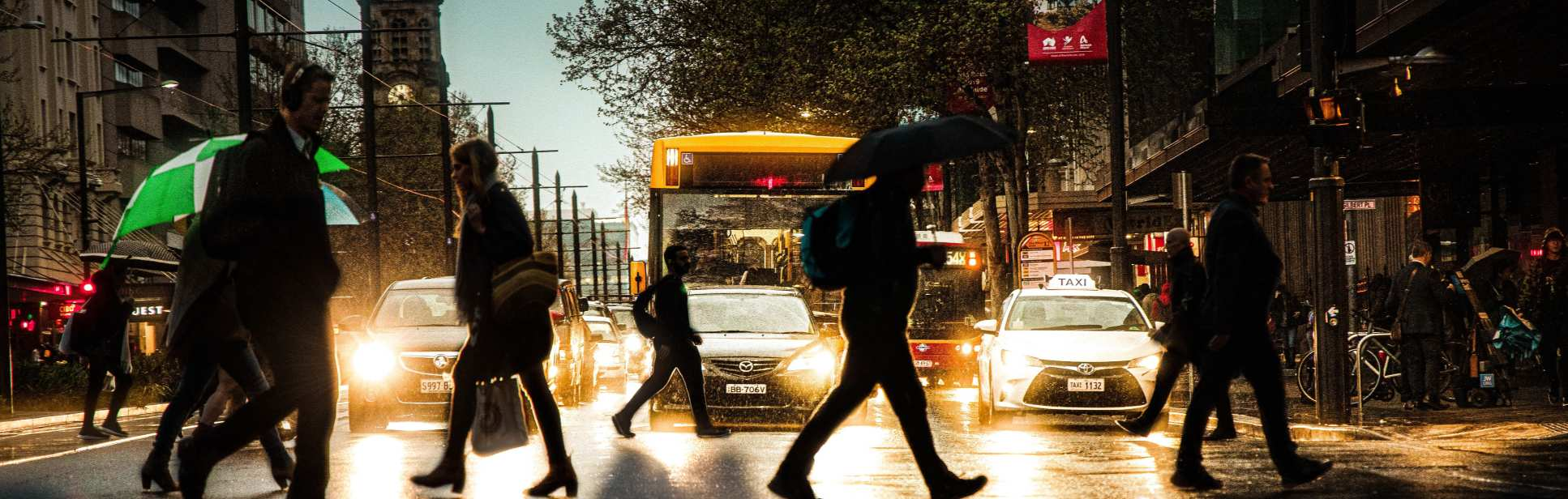 People crossing a busy road in the rain