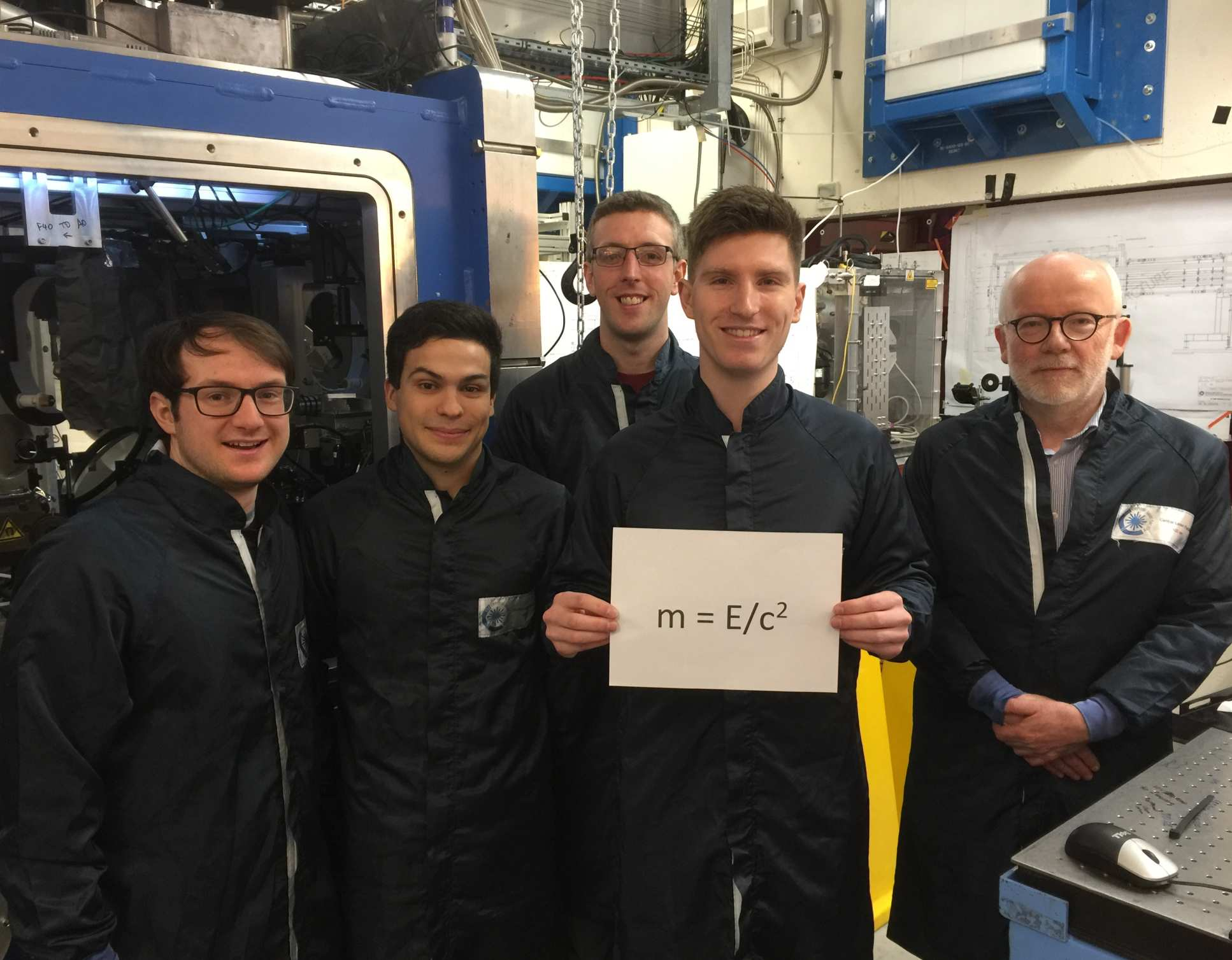 5 men in a lab holding a sign that says m=E/c2