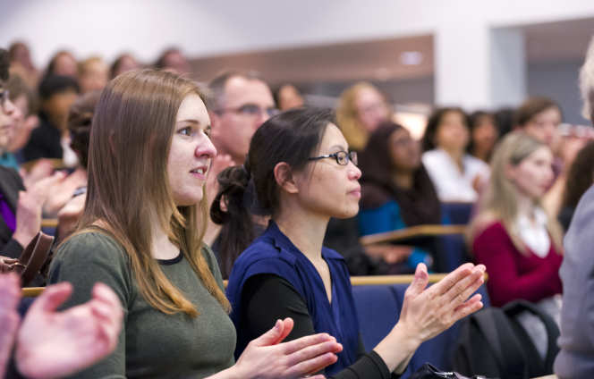 Female academics clapping