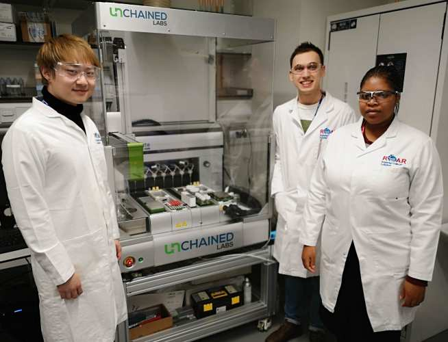 Simeng, Valerie and Roddy with one of ROAR's high-throughput robotic reactors