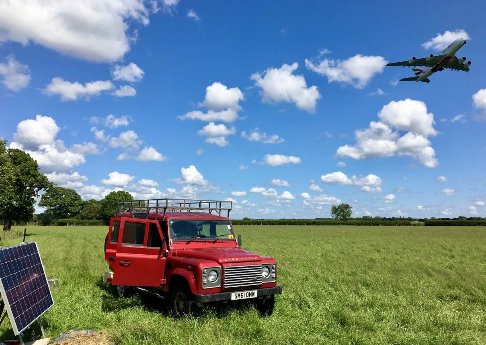 Photo showing car in field in foreground and plane taking off in background