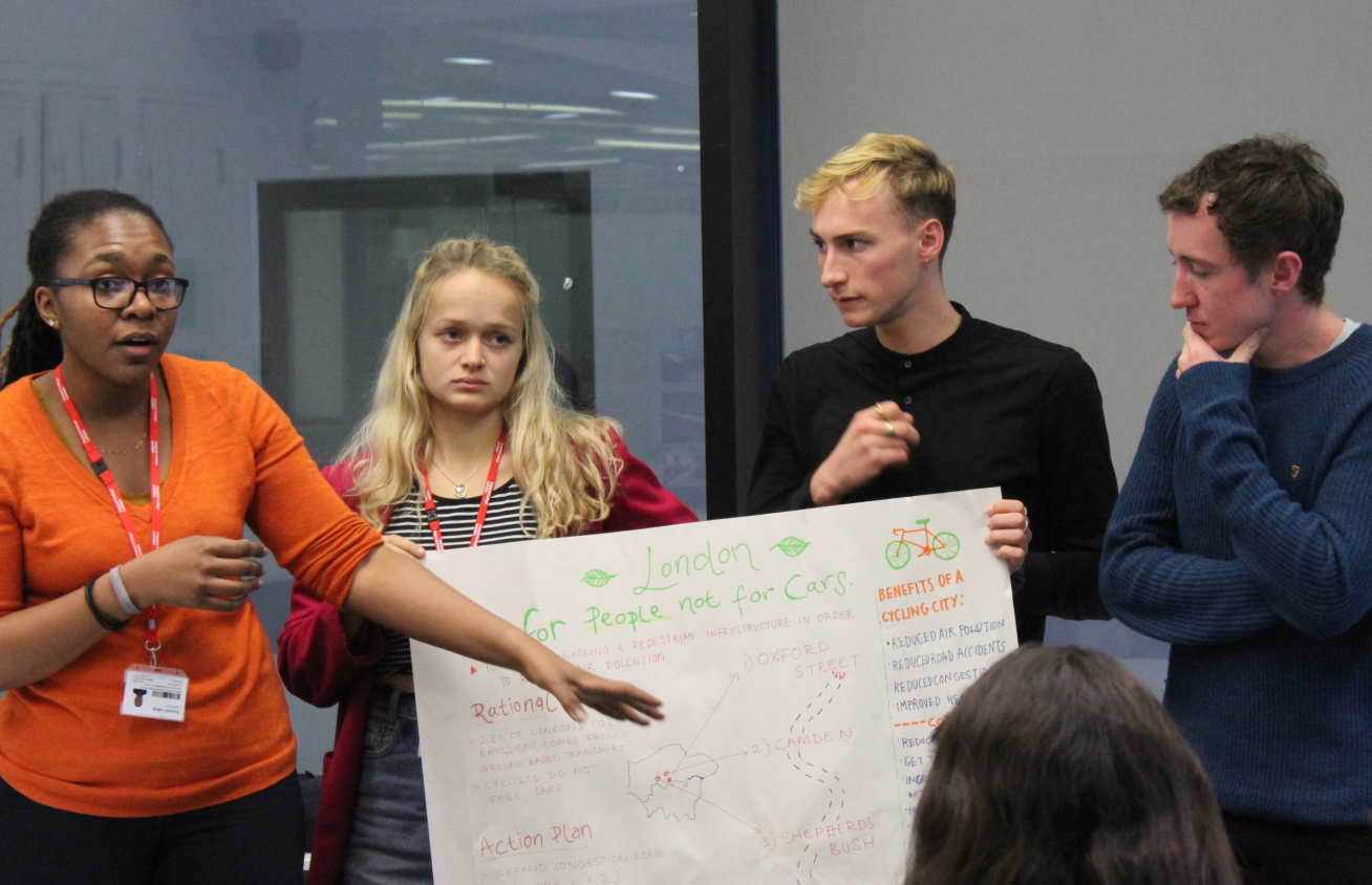 Four students present a colourful poster in front of a room of their peers