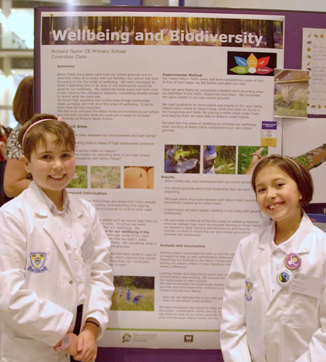 "Photo of two children in lab coats presenting their work in front of a poster titled ""Wellbeing and Biodiversity"""