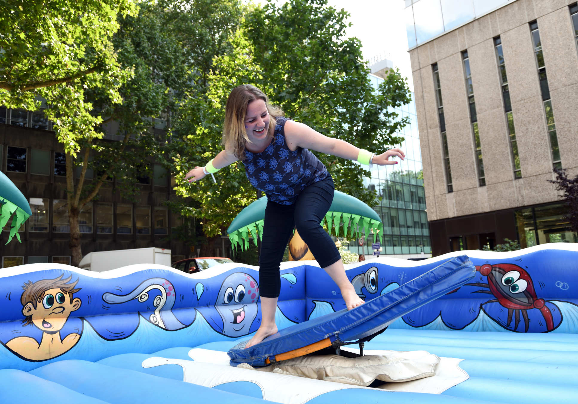 A staff member tries out surfing on an inflatable surfboard