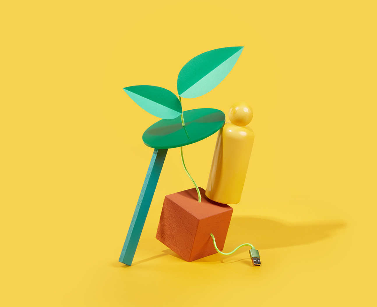 A digital illustration of a green plant connected to an orange cube by a USB cable and a yellow playing piece representing a human form perched on top precariously