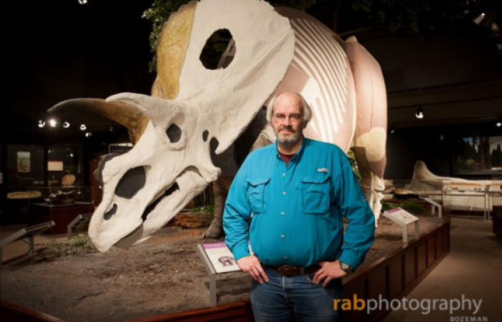 Jack Horner standing in front a replica of a triceratops