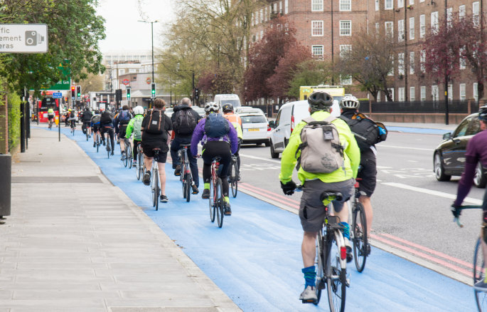 cyclists in cycle lane alongside a road