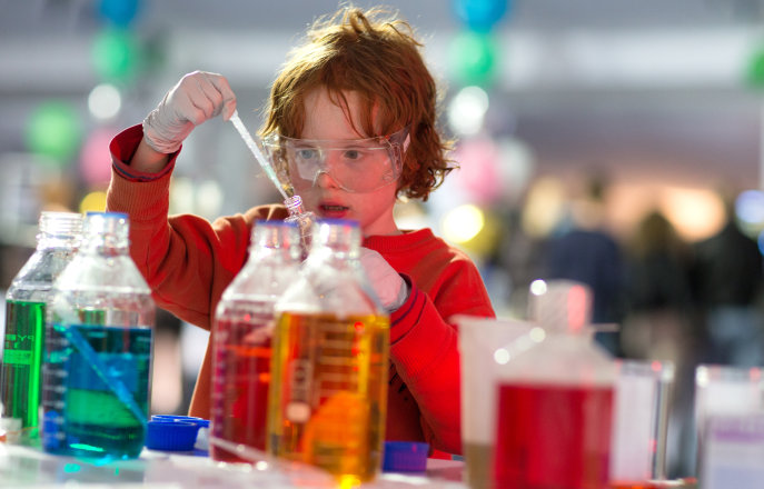 Kid in a lab doing an experiment