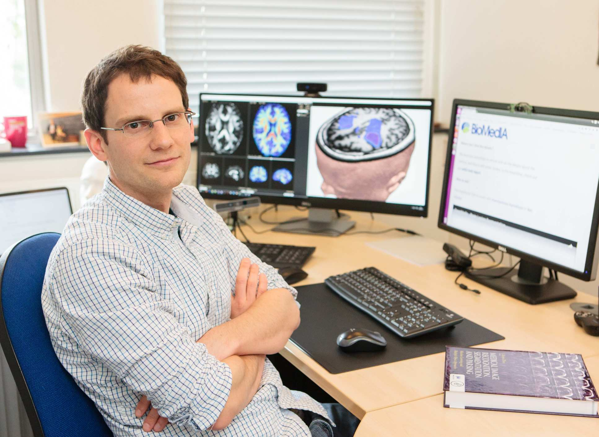 Dr Ben Glocker seated at a computer showing medical scans