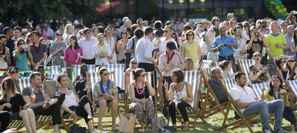 Imperial College staff sat on deckchairs and standing on the Queen's Lawn at the Summer party