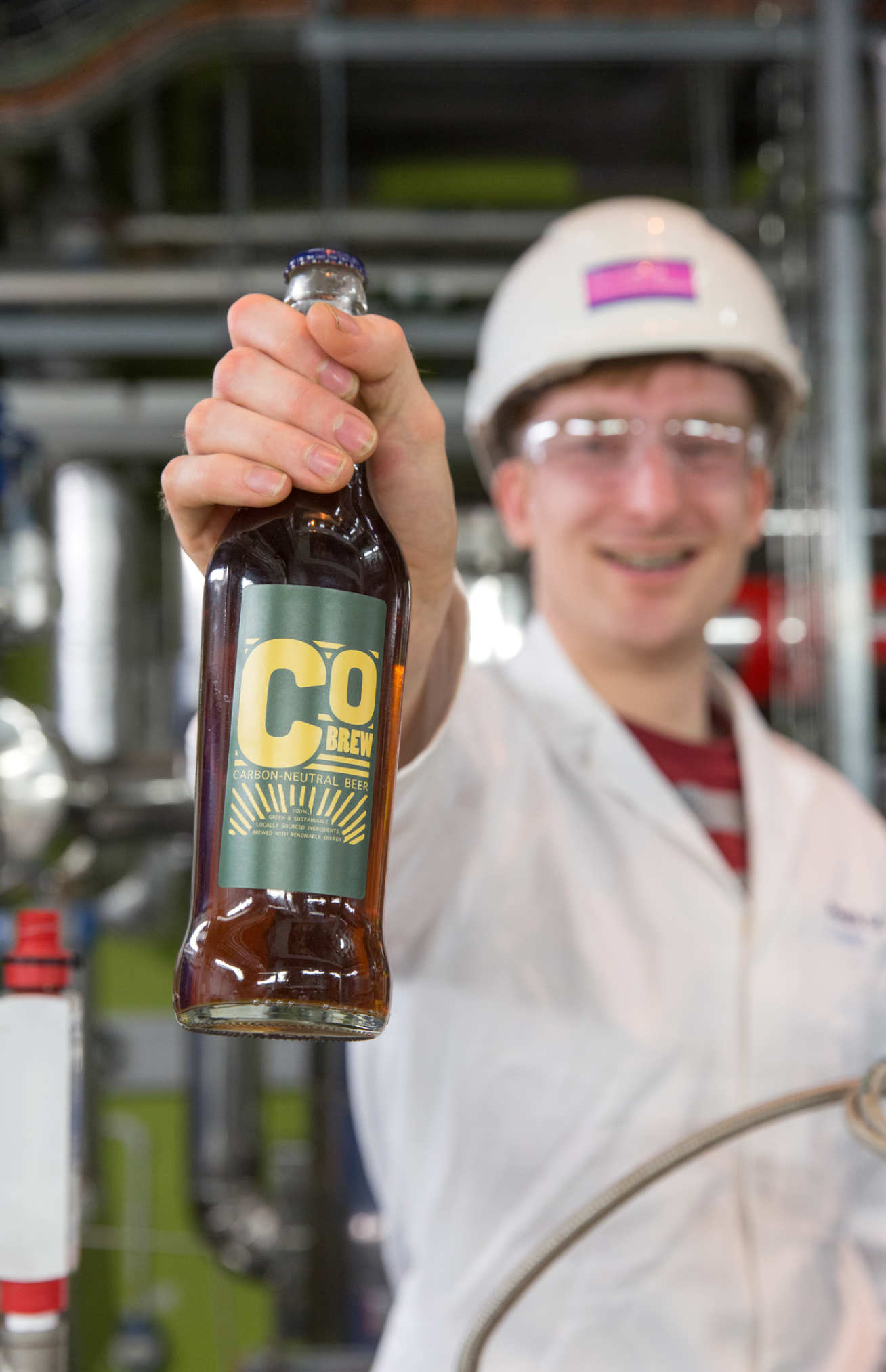 Matt Barker holds a bottle of the CObrew beer in the Carbon Capture Pilot Plant