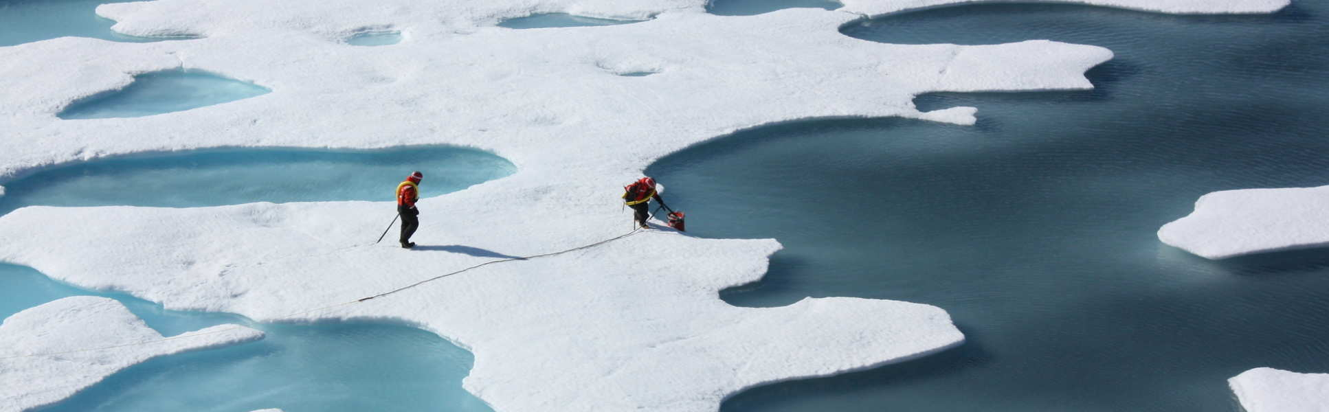 Crew from the U.S. Coast Guard Cutter Healy on ice surrounded by water, retrieving a canister
