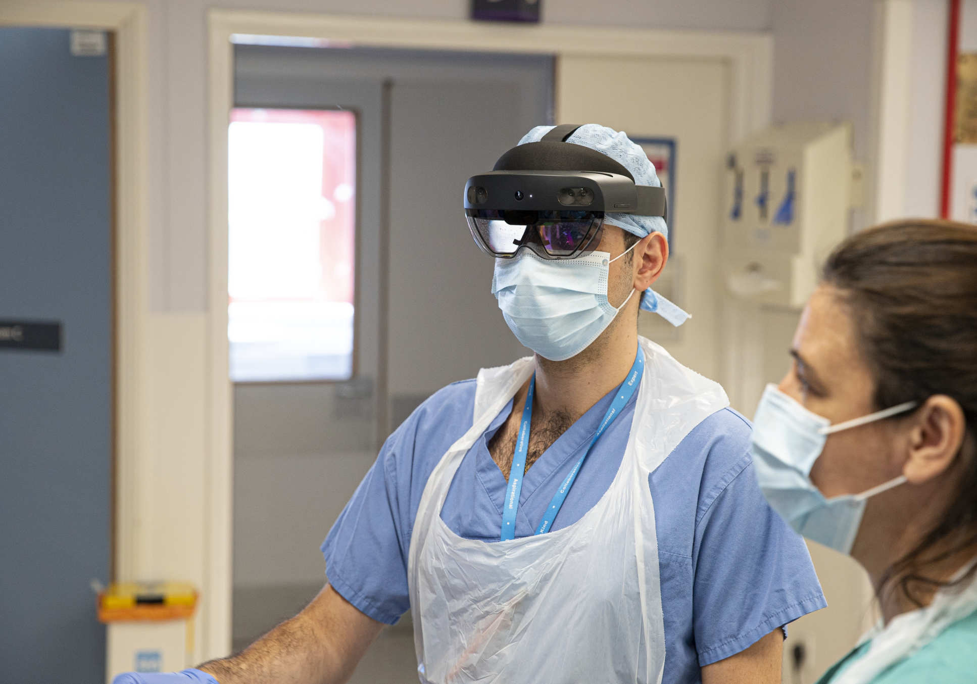 A photogrph of two doctors, one wearing a HoloLens headset