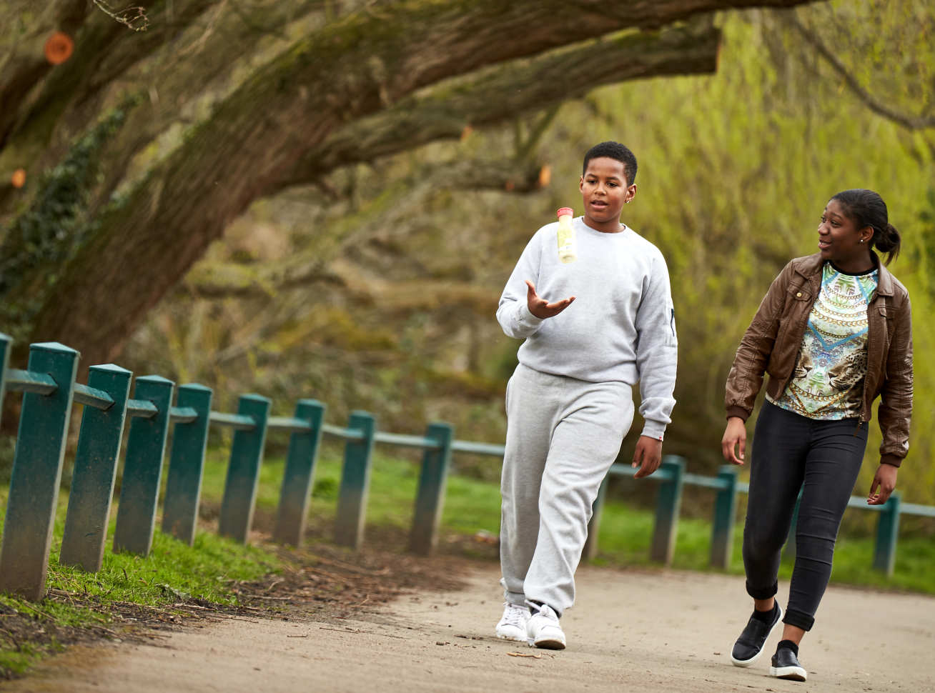 An overweight young man walks in a park