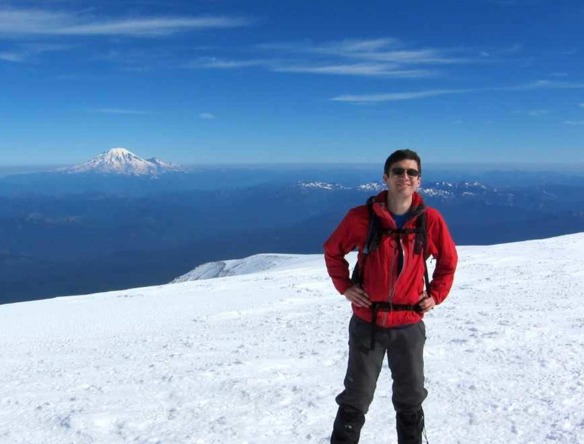 Dr Ceppi on top of Mount Adams, with Mt Rainier in the background