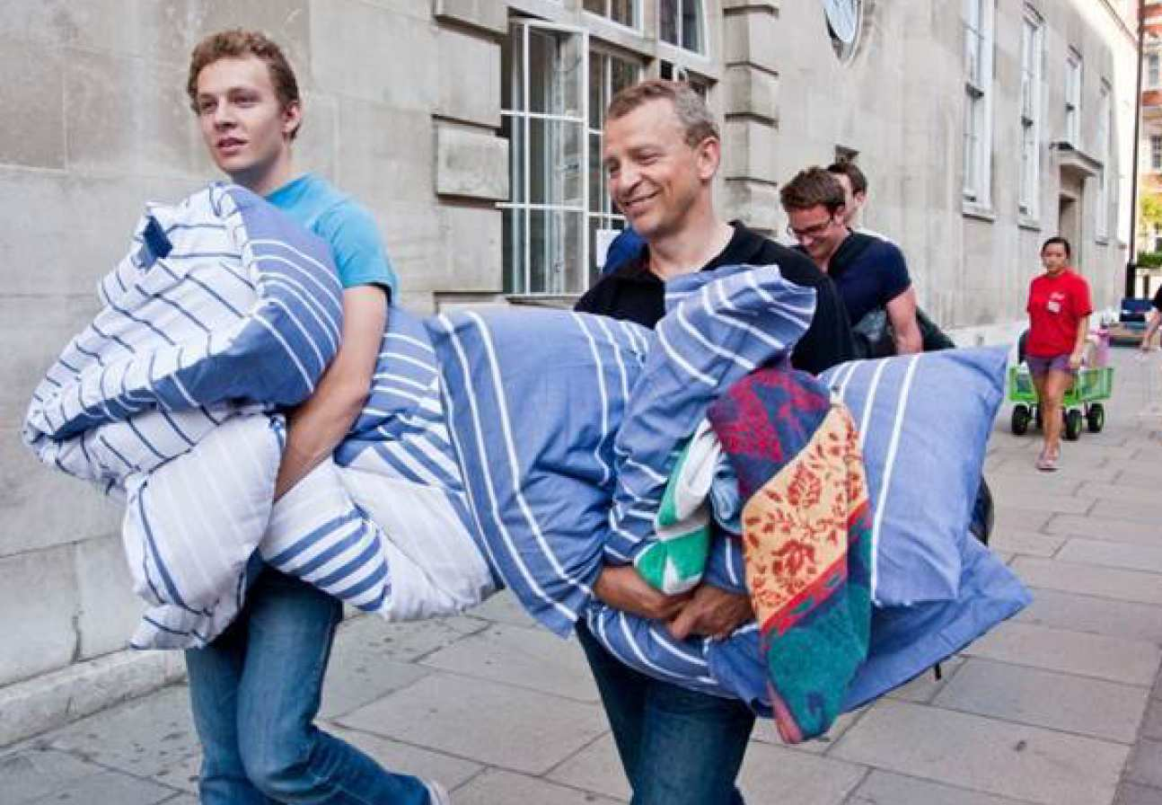 Student and parent carrying bedding