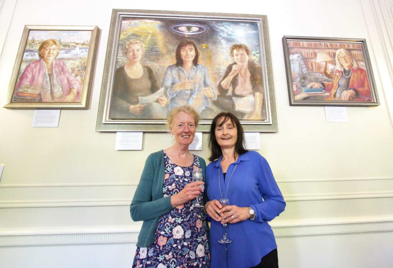 Jo Haigh and Michele Dougherty holding wine glasses in front of a painting of themselves