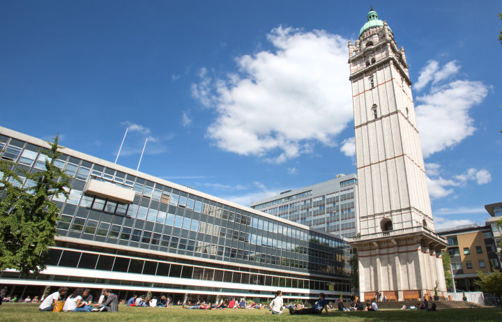 Photo of the Queen's Tower and lawn with students enjoying the spring sunshine