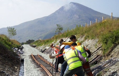 Partially complete railroad being built towards mountain