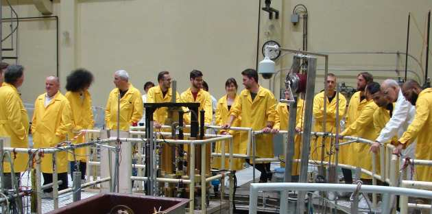 A group of students, academics and technical staff standing over a research reactor in Romania