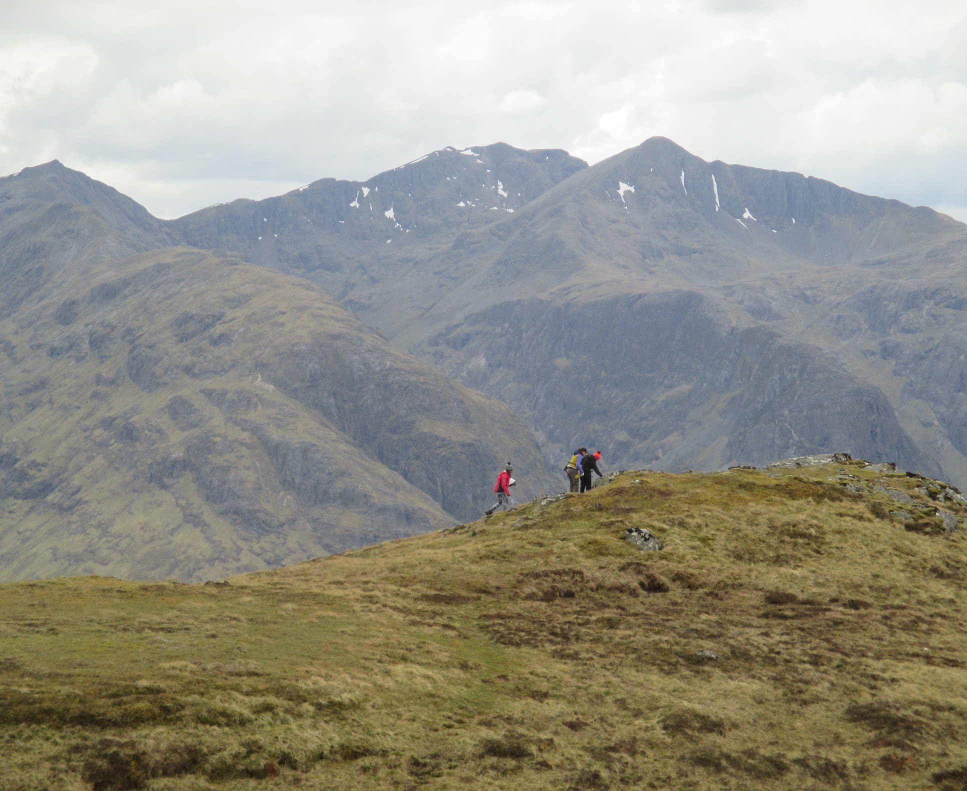 Three students walk across ridge of a mountain, with peaks in the background on a field trip to Scotland in 2017