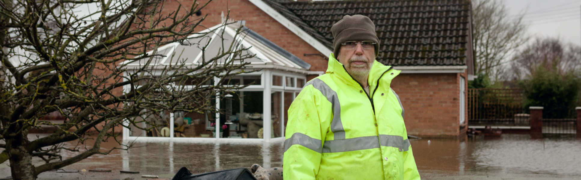 man in high viz standing thigh deep in flooded surroundings with house behind him