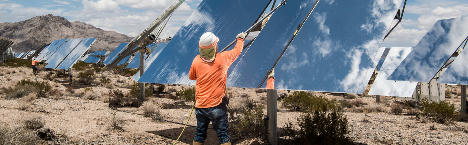 man cleaning big solar panels installed on the floor in arid conditions